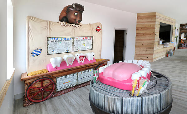Western wagon themed educational area with tooth brushing station and cavity station.