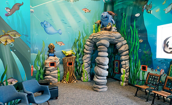 A manatee themed play area with video games and a cave for kids to play inside.