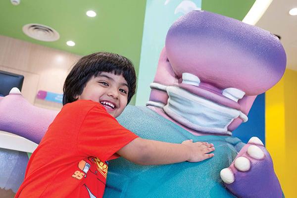 kid-hugging-clinic-mascot-sculpture
